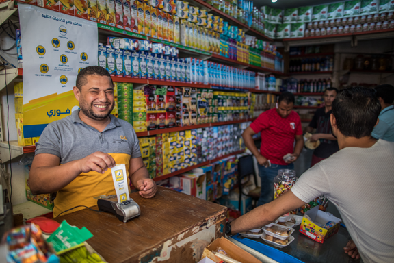 Shop owner using Fawry POS system. Photo credit: Oliver Weiken, IFC